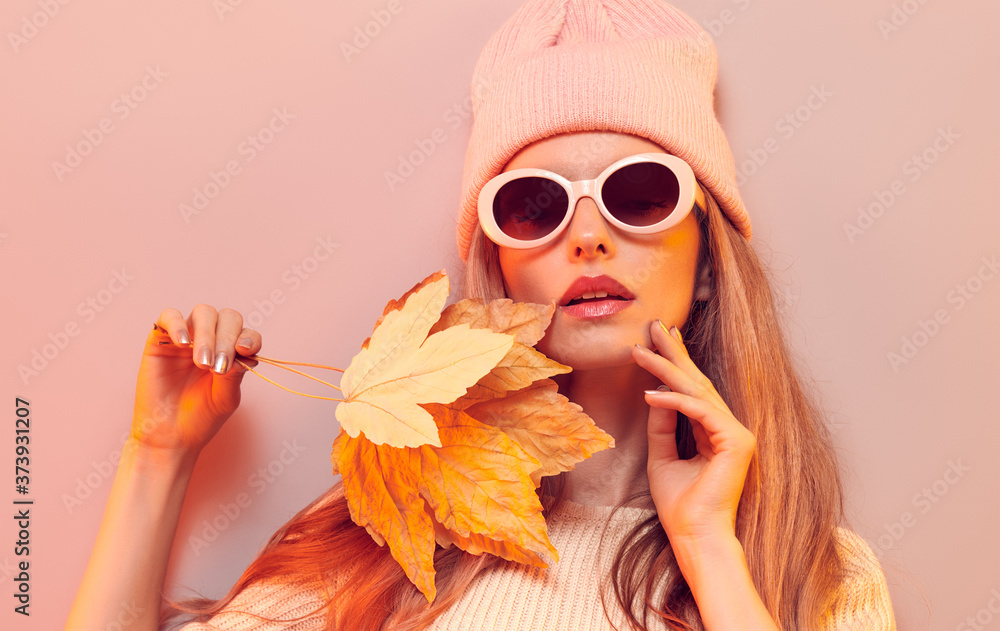 Fototapeta Fashionable hipster woman in Trendy autumn fall outfit, stylish hair, makeup. Blonde model in jumper, fashion jeans having fun smiling. Beautiful girl in autumnal beanie hat with maple leaf