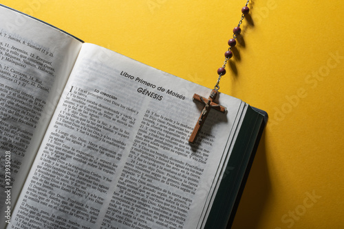 Foto Open Bible in spanish at Moses first book Genesis and rosary over yellow flat lay