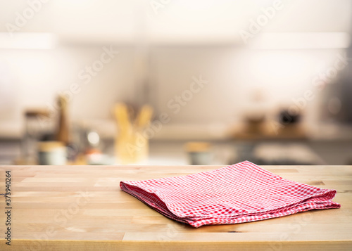Foto Red fabric,cloth on wood table top on blur kitchen counter (room)background