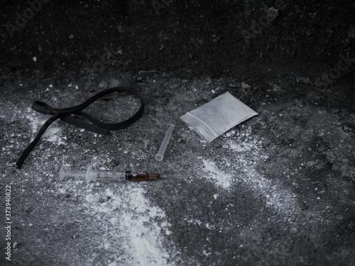 Heroin in syringe and powder heroin in plastic bag pack with rubber band on dirty cement floor Billede på lærred