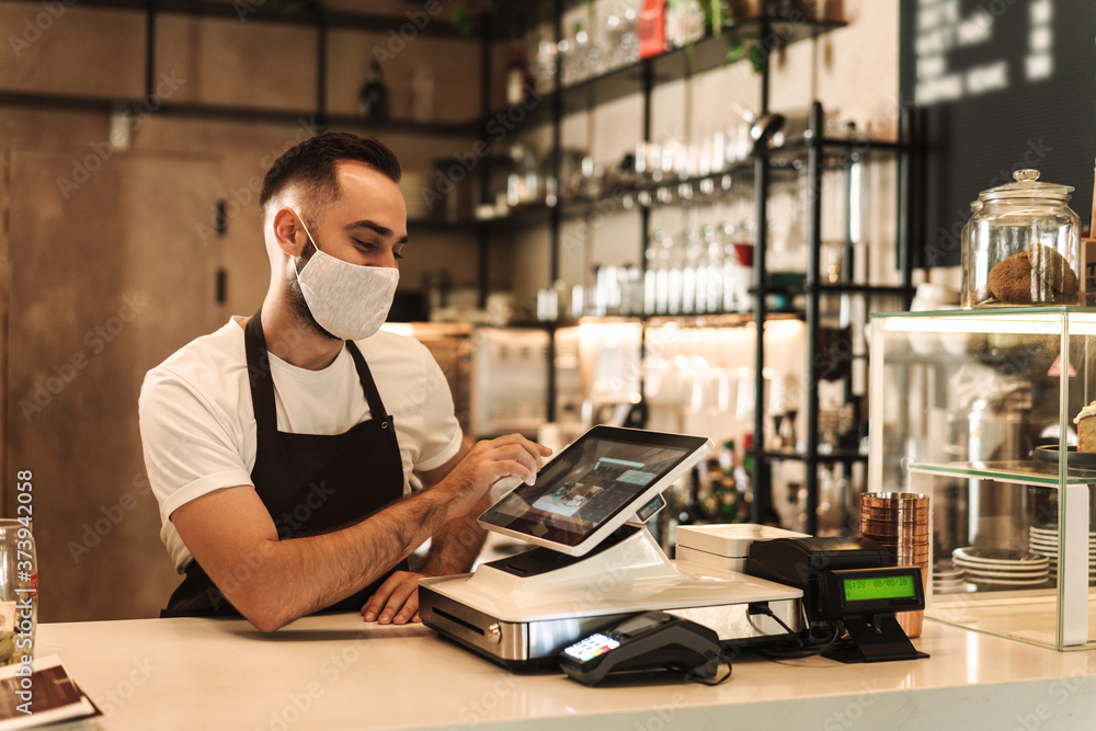 Barista with face mask in coffee shop, lockdown, quarantine, coronavirus, back to normal concept