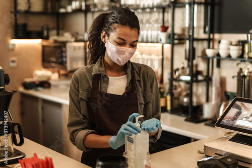 Fototapety, obrazy: Woman with face mask standing at the counter