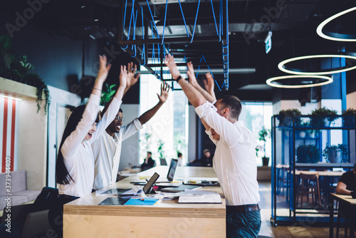 Vászonkép Amused multiracial office workers cheering with hands up while standing by desk