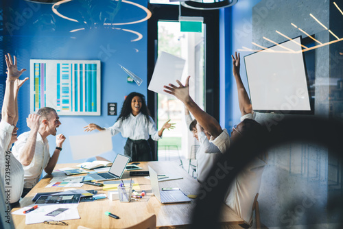 Excited ethnic businesswoman announcing good news to happy multiethnic coworkers Wallpaper Mural