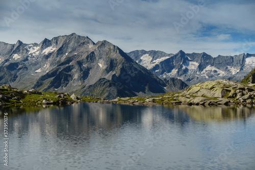 Fotografie, Obraz Bergsee mit Spiegelung eines Gebirges im Hintergrund in Tirol Österreich