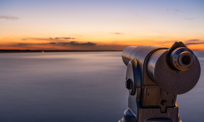 A telescope on a lookout at a beautiful sunset and a long exposure of the water on the sea.