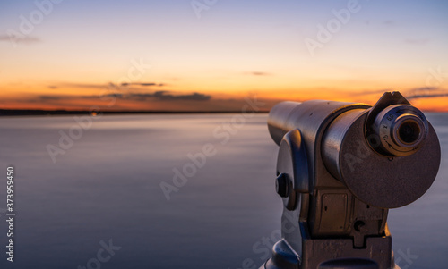 Fotografie, Obraz A telescope on a lookout at a beautiful sunset and a long exposure of the water on the sea