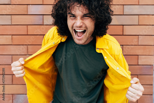 Obraz na plátne Half-length shot of cheerful young man with curly hair has joyful expression, posing for social advertisement against brick wall in the city street