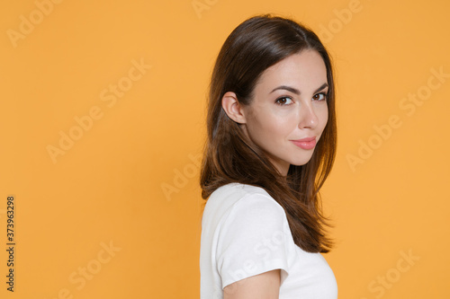 Obraz na plátně Side view of smiling beautiful attractive young brunette woman 20s in white blank empty design casual t-shirt posing standing looking camera isolated on yellow color wall background studio portrait