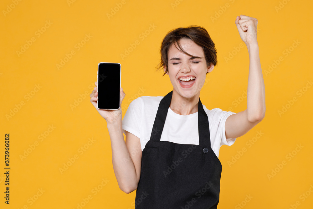 Fototapeta Happy young female woman 20s barista bartender barman employee in apron hold mobile phone with blank empty screen mock up copy space doing winner gesture isolated on yellow background studio portrait.