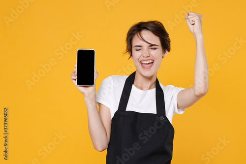 Leinwand Poster Happy young female woman 20s barista bartender barman employee in apron hold mobile phone with blank empty screen mock up copy space doing winner gesture isolated on yellow background studio portrait