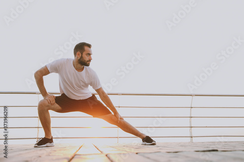 Obraz na plátne Full length portrait of handsome young bearded athletic man guy 20s in white t-shirt posing training doing stretching lunge exercising for legs looking aside at sunrise over the sea outdoors