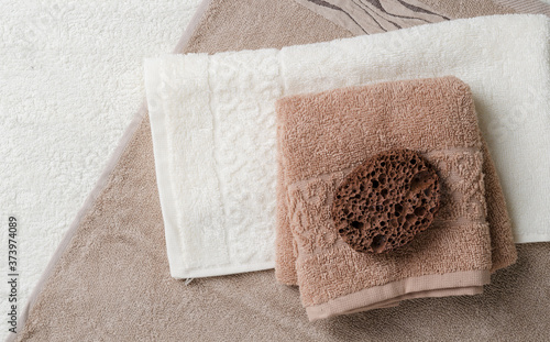 Fotografia Two towels are stacked on a spread out beige towel