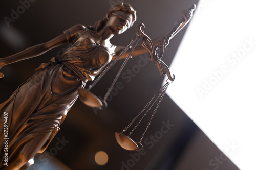Scales of Justice, Justitia, Lady Justice and Law books in the background Canvas Print