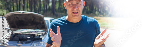 An agitated man next to his broken car. Canvas Print