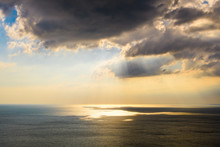 Large Dark Clouds Over The Sea. The Sun's Rays Shine Through The Clouds And Are Reflected On The Sea.