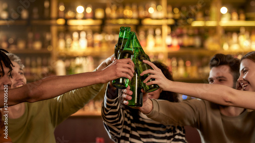 Photo Close up of hands of people in the bar clinking bottles while drinking beer together