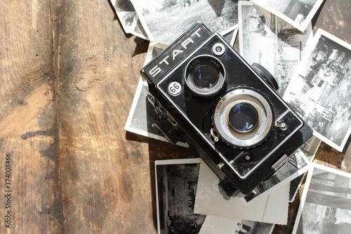 Polski powojenny aparat fotograficzny, obok rozrzucone czarno-białe zdjęcia