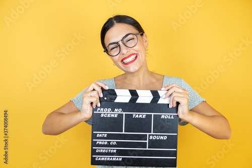 Photo Young beautiful woman wearing glasses standing over isolated yellow background h