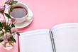 canvas print picture - above view for pink desk with red diary of notepad and tea cup on it. table decorated with flowers. office workplace background backdrop