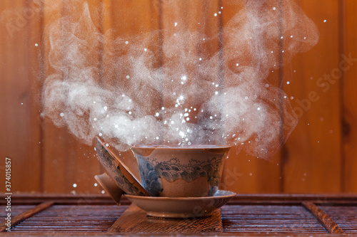 Photo Traditional chinese painted clay tea brewing cup with cloud of steam and splashi