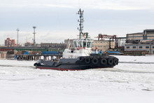 Tug Ship Goes Through The Frozen Canal In The Industrial Port After The Icebreaker