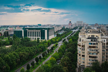 Seat Of Romanian Parliament, Huge Building In The Centre Of Bucharest, Romania On A Cloudy Summer Day. View Over The Avenue Looking Towards Parliament