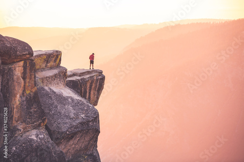 Tela A male hiker stands at the edge of a cliff at Taft Point, Yosemite National Park