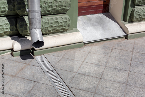 Photo urban engineering structure downspout on green facade building with drainage grate of gray stone granite sidewalk from square tiles with copy space, closeup details city infrastructure, nobody
