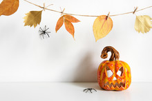 Halloween Composition With Ceramic Pumpkin Jack Lantern And Floral Garland On Table Wall Background. Home Decoration