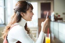 カフェでスマホを見る女性