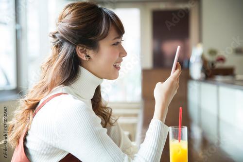 Fotografia カフェでスマホを見る女性