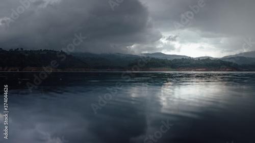 Fényképezés Lago con cielo nublado y nubes oscuras