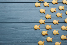 Delicious Goldfish Crackers On Blue Wooden Table, Flat Lay. Space For Text