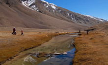 Four Persons Walk In A Valley On A Clear Day  - A Narrow Stream Of Water Flows With Reflections Of Valley Hills On It.