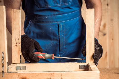 Fotografie, Obraz Close-up of a man with work clothes, a carpenter drilling a wooden board with sc