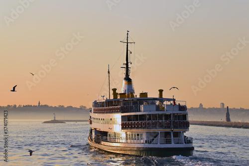 Fototapeta Ferry sailing along the Bosphorus Strait at sunset