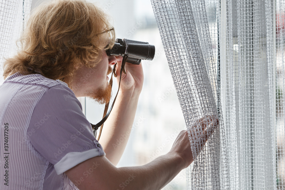 Fototapeta Man with binoculars spying on neighbors