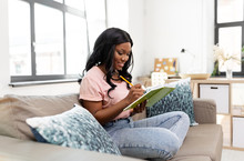 People, Inspiration And Leisure Concept - Happy Smiling African American Woman With Diary Sitting In Chair At Home