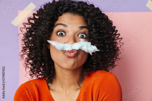 Vászonkép Image of amusing african american woman making fun with cotton candy