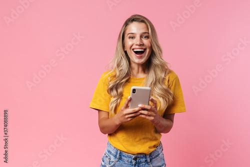 Positive young woman using mobile phone Tapéta, Fotótapéta