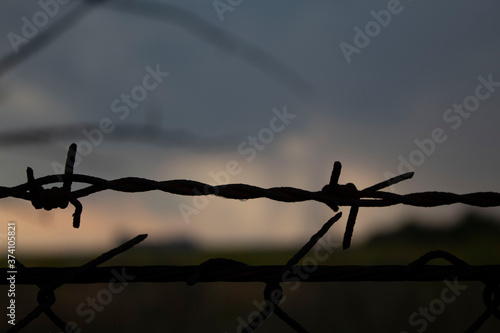 Photo Barbed wire fence, close-up, against the background of dusk
