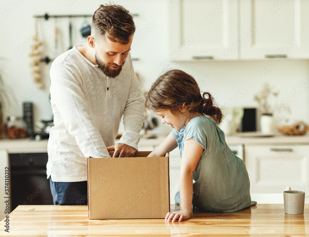 Fototapeta Father and kid unpacking carton box at home.