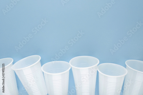 White plastic empty cups laid out in a row on blue background. Fototapet