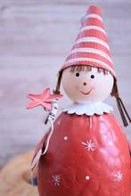 木製の壁ととんがり帽子のおさげの女の子