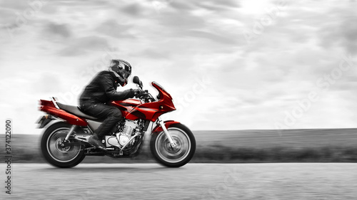 A biker rides a red motorcycle at high speed Tapéta, Fotótapéta