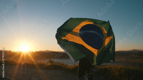 Fotografia Brazilian Girl with National Flag at sunrise