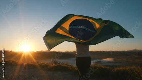 Fototapeta Brazilian Girl with National Flag at sunrise