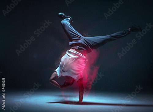 Fotomural Cool young guy breakdancer dancing hip-hop in neon light