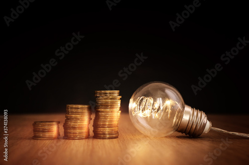 Fotografija Light bulb illuminates a stack of coins, a concept of smart investment, increase